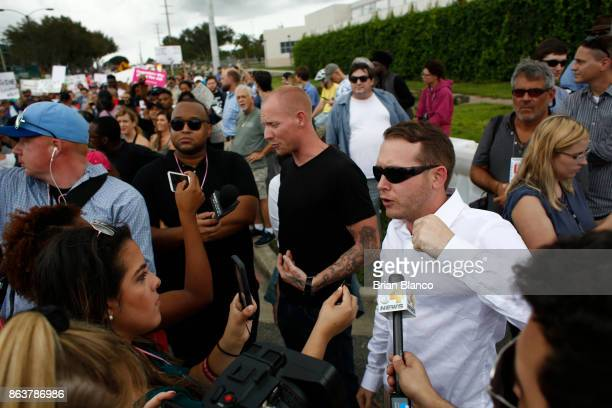 Selfdescribed white nationalist Tyler Tenbrink of Houston Texas center and friend William Fears right speak to members of the media as demonstrators...