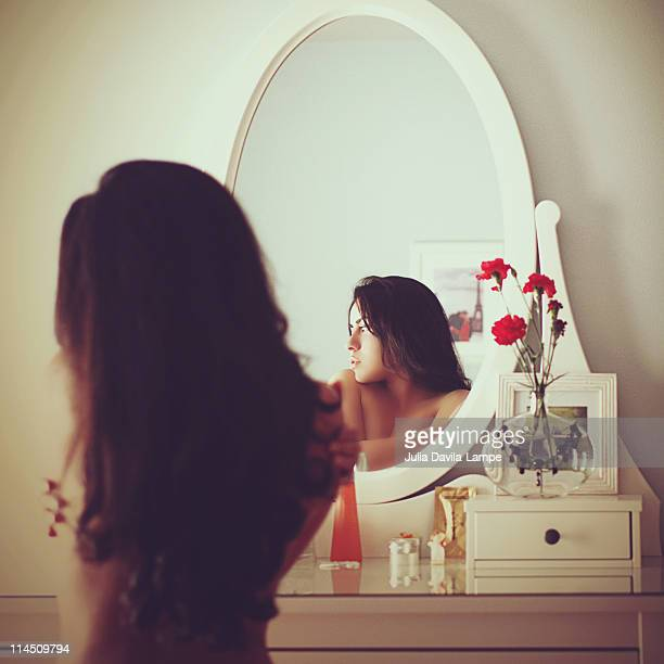 Self-embrancing woman in front the mirror.