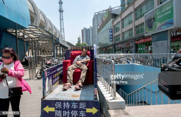 A selfemployed freight man naps on his little truck outside a small commodity market To ease Beijing's noncapital functions and upgrade industrial...