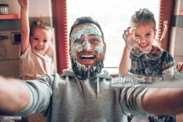 selfie by father with cute child daughters after cooking and making mess with topping - bizarre stock pictures, royalty-free photos & images