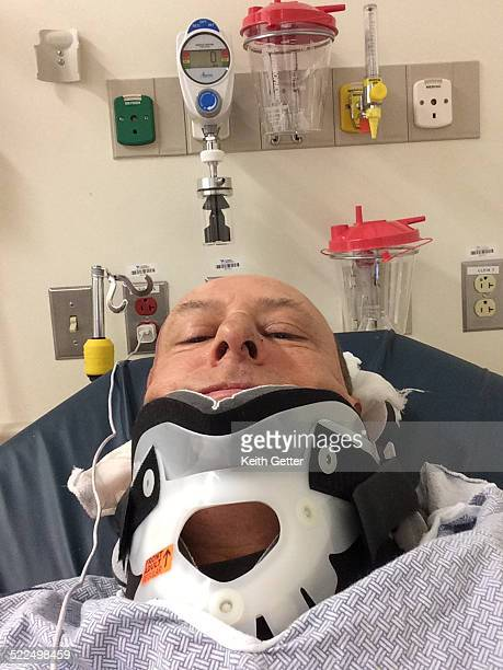 'Selfie' Image Showing a Man in Emergency Room Trauma Center on a Hospital Bed Wearing a Hospital Gown with a Protective Neck and Spinal Collar and...