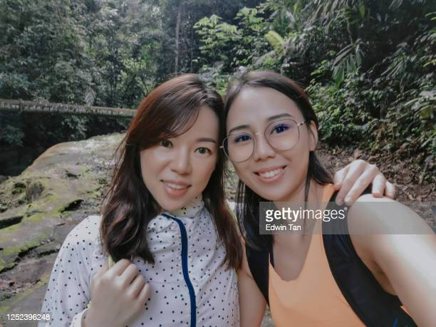selfie of 2 asian chinese female hiker in the jungle looking at camera - sister stock pictures, royalty-free photos & images