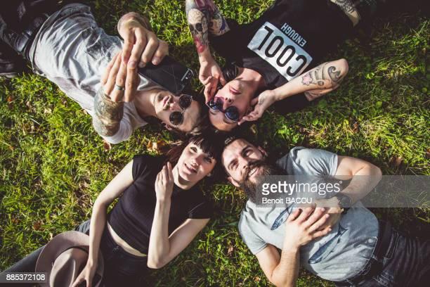 selfie of a group of young hipster lying in the grass - cuatro personas fotografías e imágenes de stock
