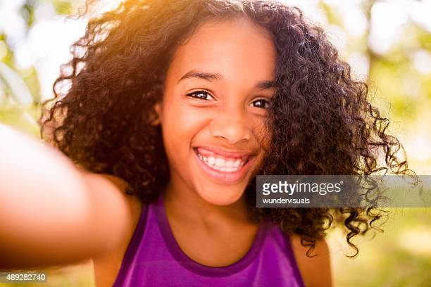Selfie of a preteen Afro girl smiling happily