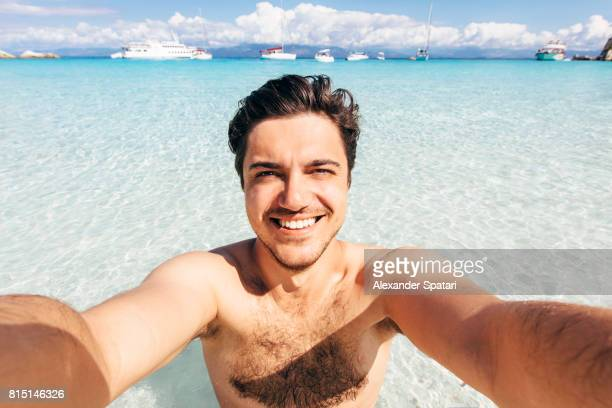 Selfie of a young handsome man on the beach in Greece