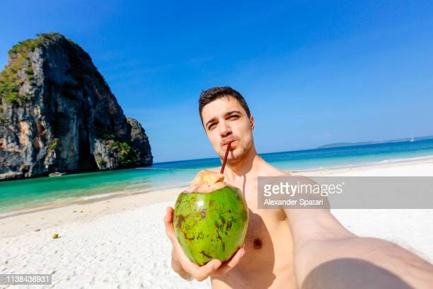 selfie of a young man drinking coconut on the beach on a sunny day - strandurlaub stock-fotos und bilder