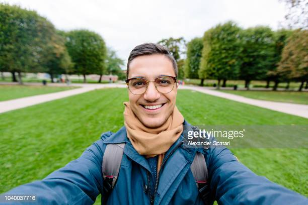 selfie of a young man in eyeglasses in a park - grande angular - fotografias e filmes do acervo