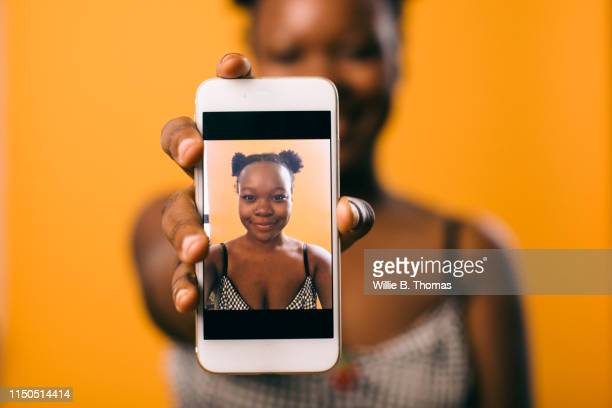 selfie of black woman on smartphone - halten stock-fotos und bilder