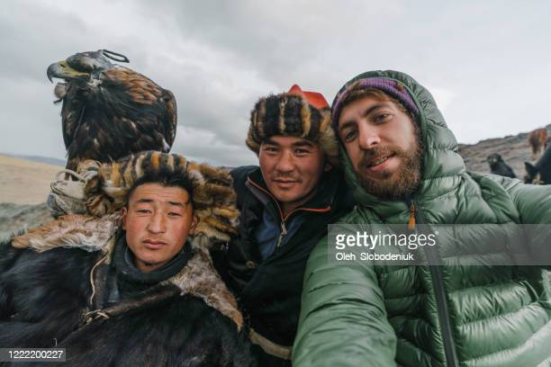 selfie of caucasian man with eagle hunters in mongolia - mongólia imagens e fotografias de stock