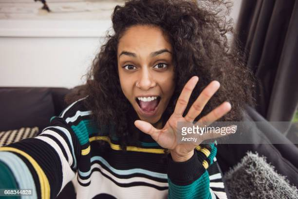 selfie of charming woman waving to camera - waving gesture stock photos and pictures