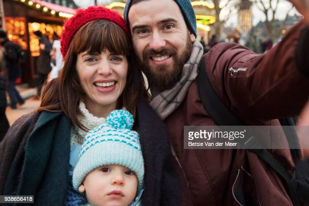 Selfie of family at christmas market, outdoors.