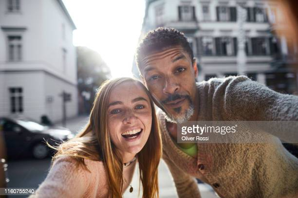 selfie of father and adult daughter in the city - fotohandy stock-fotos und bilder