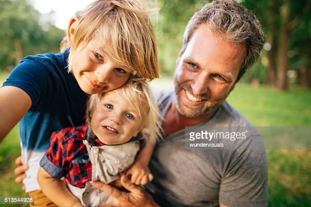 Selfie d'un père et ses deux fils dans le parc