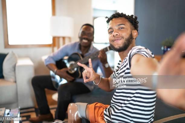 selfie di padre e figlio che suonano musica in salotto - disabilitycollection foto e immagini stock