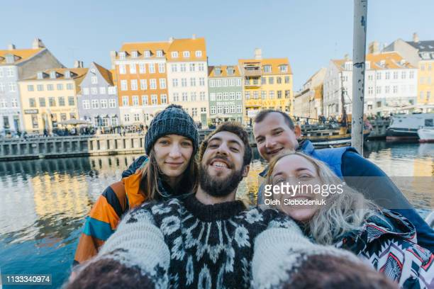 selfie of four friends on the background of colorful street in copenhagen - denmark stock pictures, royalty-free photos & images