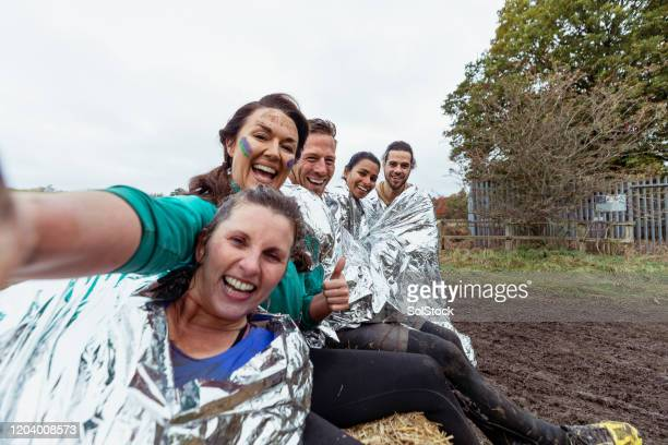 selfie of friends with foil blankets sitting on hay bale - 30 39 years stock pictures, royalty-free photos & images