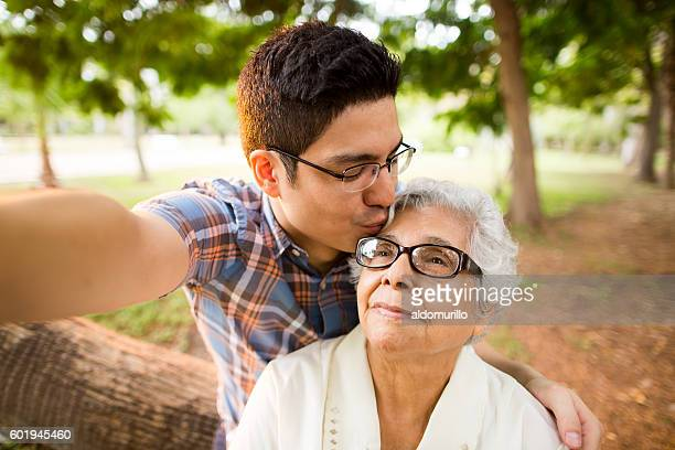 Selfie of grandson kissing grandmother on forehead