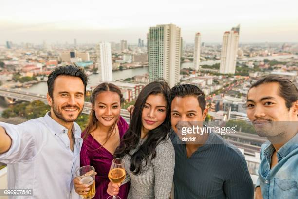 Selfie of Group of Multi Ethnic Friends Enjoying Rooftop Sunset Drinks
