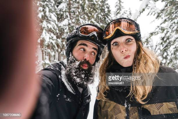 selfie of happy couple in skiwear grimacing in winter forest - ski humour photos et images de collection