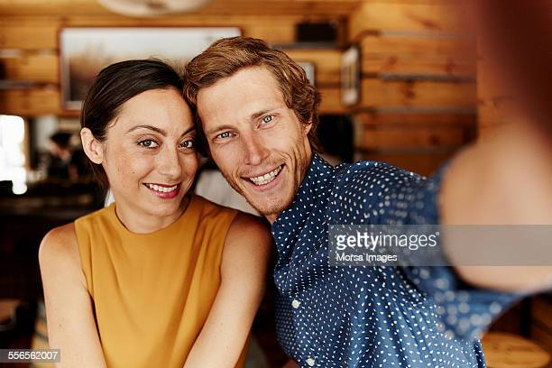 Selfie of happy mid adult couple in cafe