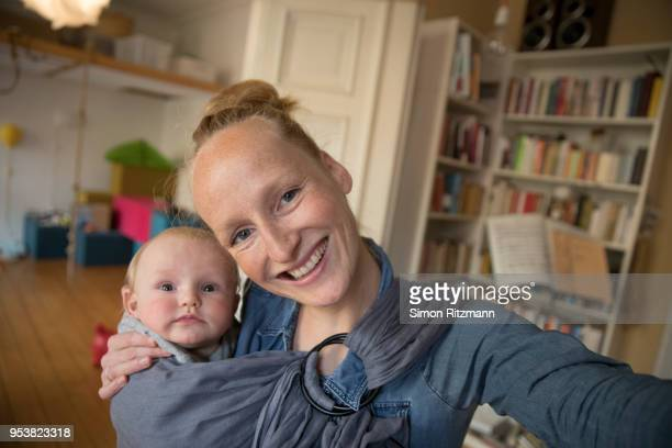 selfie of happy mother holding baby in sling at home - babyhood stock pictures, royalty-free photos & images