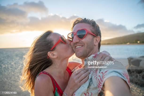 selfie d'amoureux sur la plage avec fille embrasse homme - embrasser sur la bouche photos et images de collection