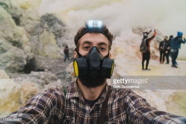 selfie dell'uomo nel vulcano ijen e nelle miniere di zolfo - vulcano attivo foto e immagini stock