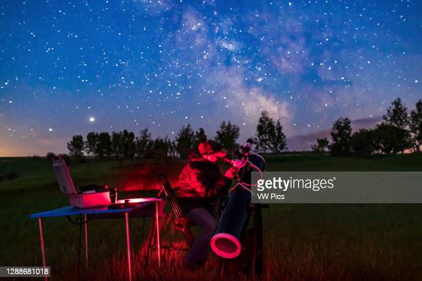 Selfie of me observing with the 20cm Sky-Watcher Dobsonian telescope on a June night in the backyard. Shot for a book illustration of accessories and...