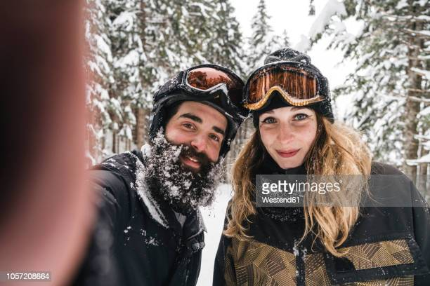 selfie of smiling couple in skiwear in winter forest - ski humour photos et images de collection