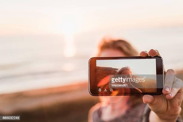 Selfie of smiling teenage girl on display of smartphone