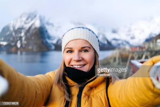 selfie of smiling tourist at hamnoy, lofoten, norway - norwegen stock-fotos und bilder