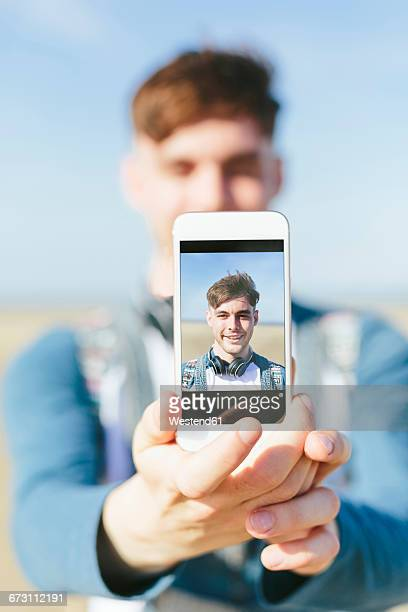 Selfie of smiling young man on display of smartphone