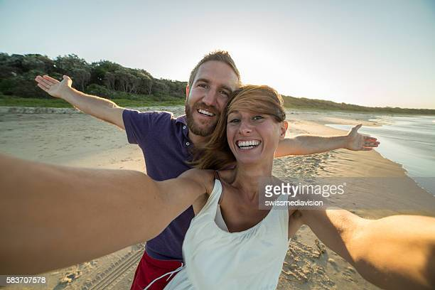 Selfie of young couple on beach at sunset
