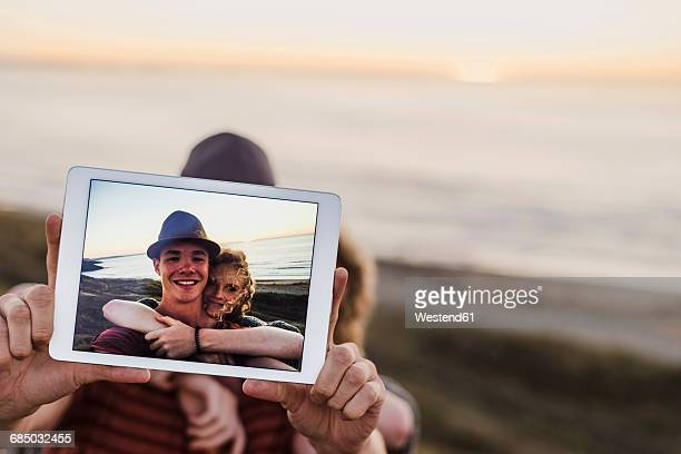 Selfie of young couple on display of tablet