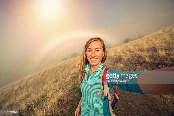 Selfie of young woman hiking, rainbow on background