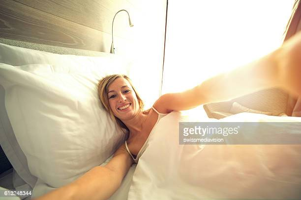 Selfie of young woman in bed in the morning