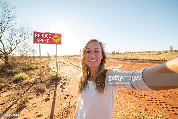 Selfie of young woman standing by Camel warning sign