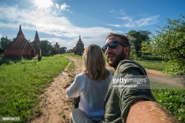 Selfie on adventure, couple rising e-bike around Bagan temples
