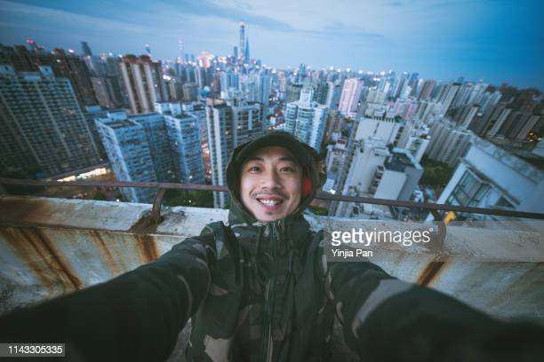 selfie portrait of man using headphones and looking at camera with smile on rooftop of tall building, shanghai, china - travel stock pictures, royalty-free photos & images