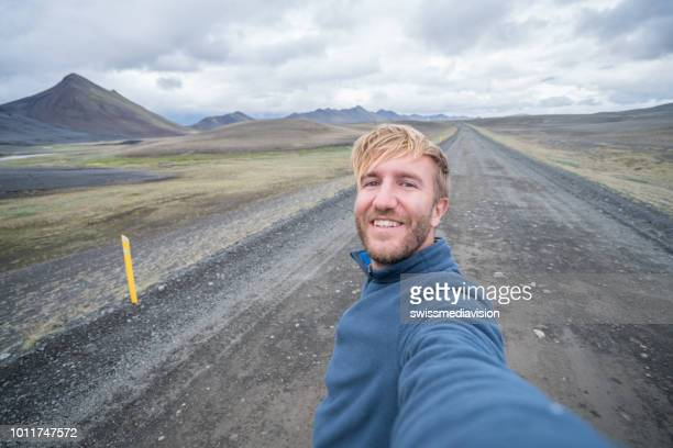 selfie portrait of tourist man in iceland at kirkjufell mountain - one man only stock pictures, royalty-free photos & images