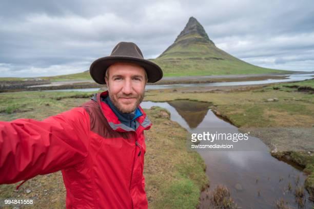 Selfie portrait of tourist man in Iceland at Kirkjufell mountain