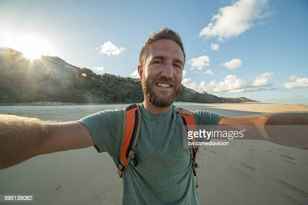 Selfie portrait of young man on beach at sunset