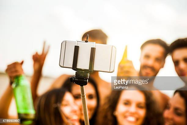 Selfie stick used by group of friend on the beach