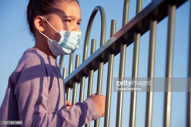 self-isolation. a kid in face mask looking away through the fence rods. - child behind bars stock pictures, royalty-free photos & images