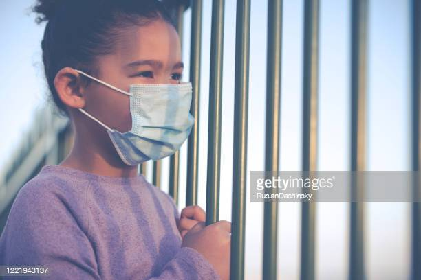 self-isolation. a kid wearing a face mask, looking away through the fence rods. - child behind bars stock pictures, royalty-free photos & images
