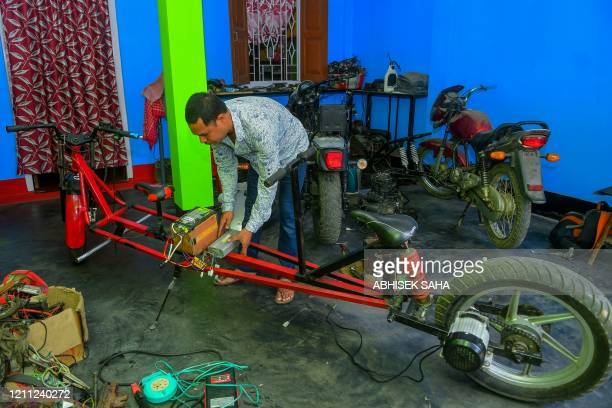 Selfmade automobile engineer Partha Saha assembles his modified bike designed for social distancing as a preventive measure against the spread of the...