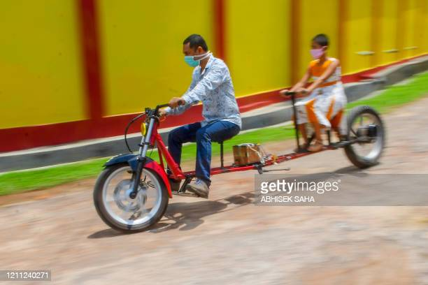 Selfmade automobile engineer Partha Saha tries his modified bike designed for social distancing as a preventive measure against the spread of the...