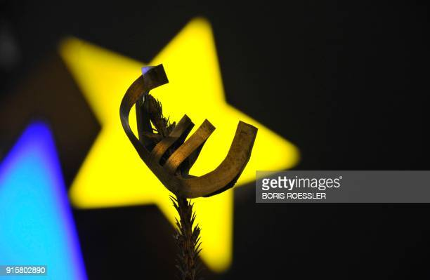 A selfmade euro sign is attached to the tip of a christmas tree in front of the sculpture by German artist Ottmar Hoerl's depicting the Euro at the...