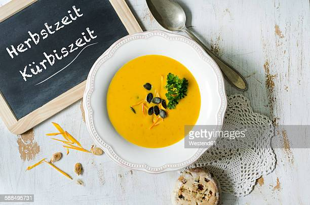 Selfmade pumpkin soup with pumpkin seeds, parsley, a slate and a bun of olives and tomatoes on a wooden table