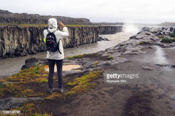 Selfoss: tourist taking picture in the rain
